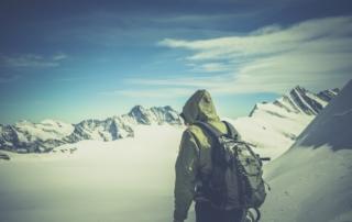 Mann wandert auf einem schneebedeckten Berg