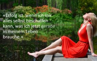 Frau mit rotem Kleid sitzt auf einem Steg an einem Waldsee.