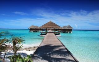 Karibischer Holzsteg der ins Wasser führt. Im Wasser sind Holzinselt mit Strohdach.