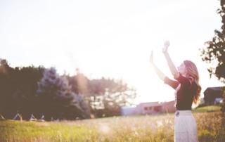 Frau steht auf einer Wiese, streckt ihre Arme in den Himmel und und geniesst die Sonne