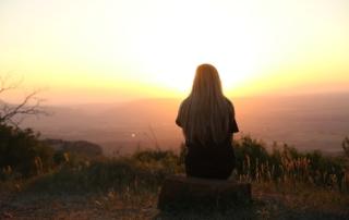 Frau, die auf einem Hügel sitzt und en Sonnenuntergang genießt