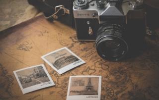 Alte Kamera auf einer Karte, daneben ein paar Polaroid-Bilder