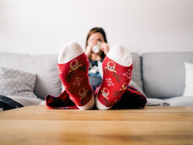 Frau legt die Füße hoch und trinkt Tee