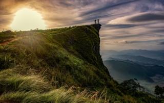 Zwei Menschen stehen auf einem begrünten Felsen und stecken ihre Arme aus und wenden sich der aufgehenden Sonne zu