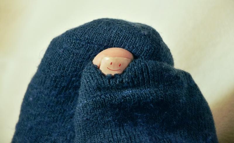 Fuß, der in einem Socken steckt und der Zeh aus einem Loch schaut. Auf dem Zehnagel ein Smiley.
