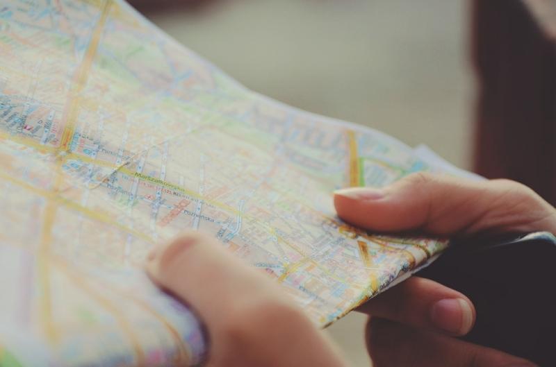 Hand, die einen Stadtplan in der Hand hält