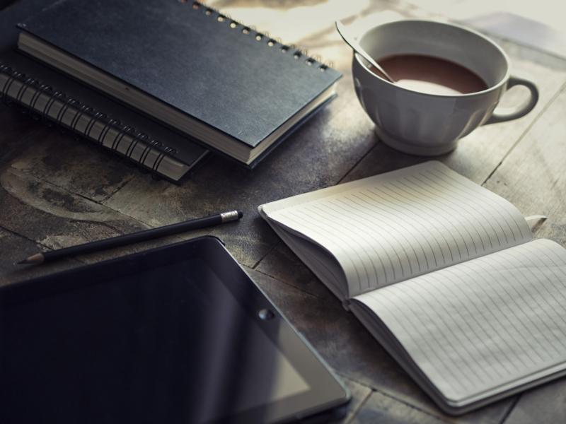 Ein leeres Büchlein auf einem Tisch, daneben eine Tasse Tee und ein iPad