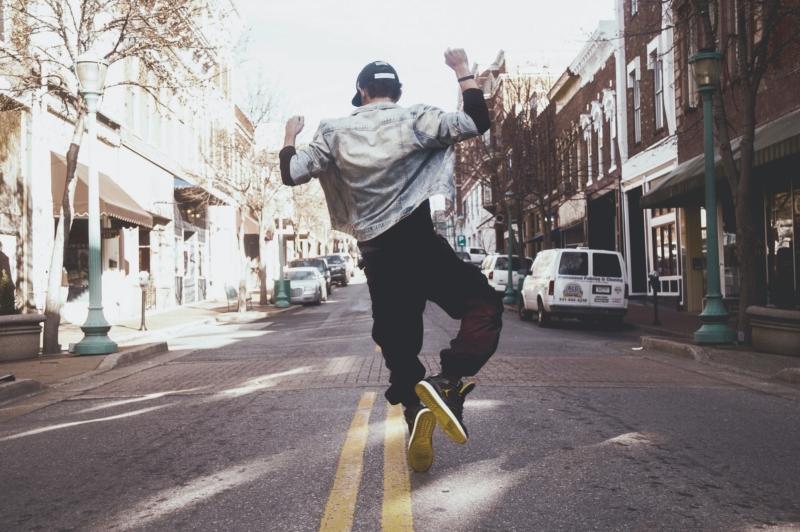 Mensch, der in die Luft springt und die Beine zusammenschlägt