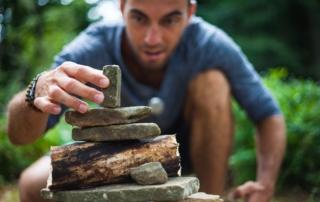 Lächelnder Mann baut einen Zen-Turm aus Steinen