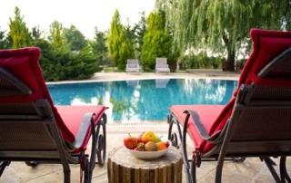 Zwei rote Liegestühle am Pool