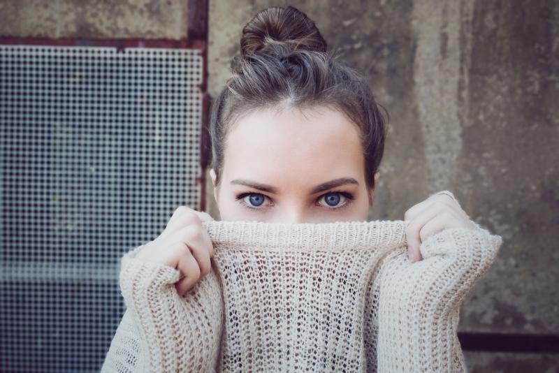 Frau versteckt sich in ihrem Pullover