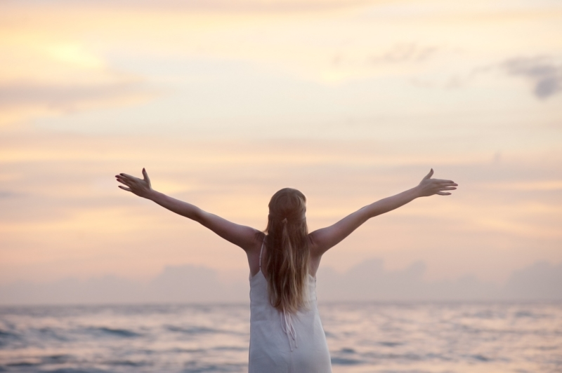 Frau am Strand, die ihre Arme ausstreckt und einen Sonnenuntergang genießt