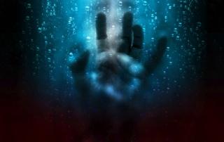 Hand, die an nasser Scheibe klebt