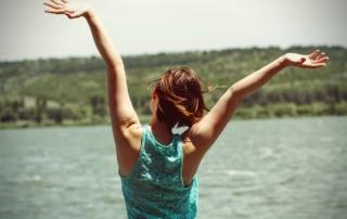 Frau streckt vor Freude die Arme in die Luft